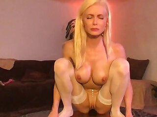 Blonde MILF in white stockings rides dildo forwards be required of webcam